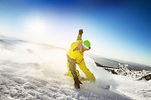 Snowboarder rides on the slope  snow mountains background