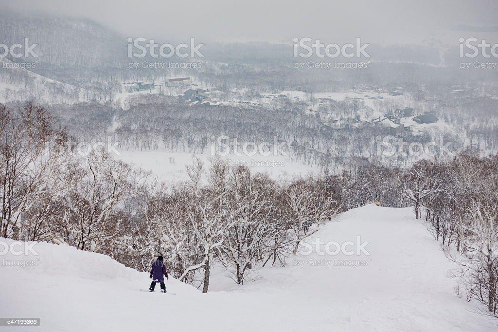 Snowboarder Riding Down the Mountain at Niseko United, Hokkaido, Japan stock photo