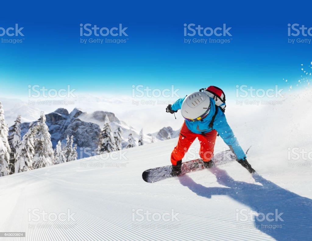 Snowboarder running downhill stock photo