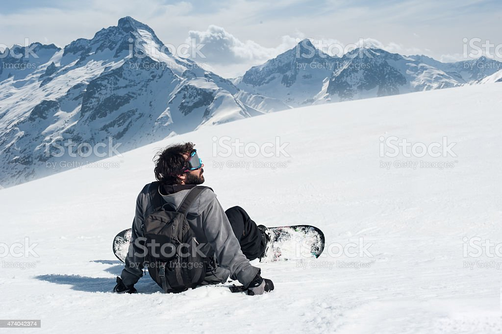 Snowboarder sit at top of mountain stock photo