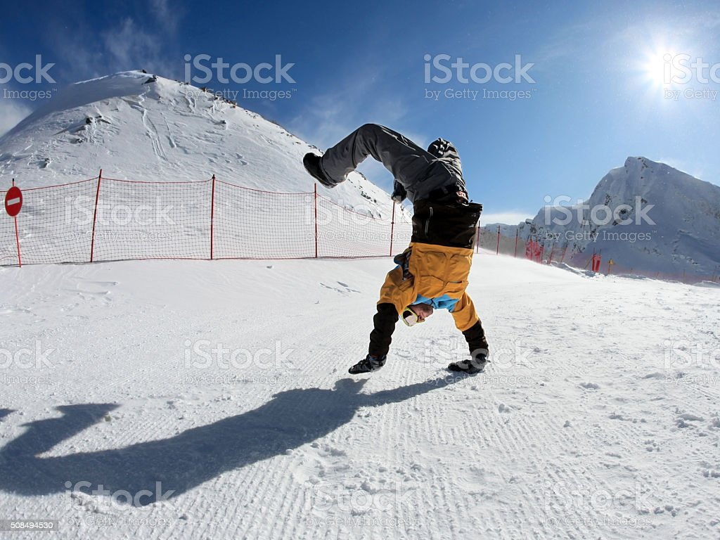 Snowboarder standing on hands stock photo