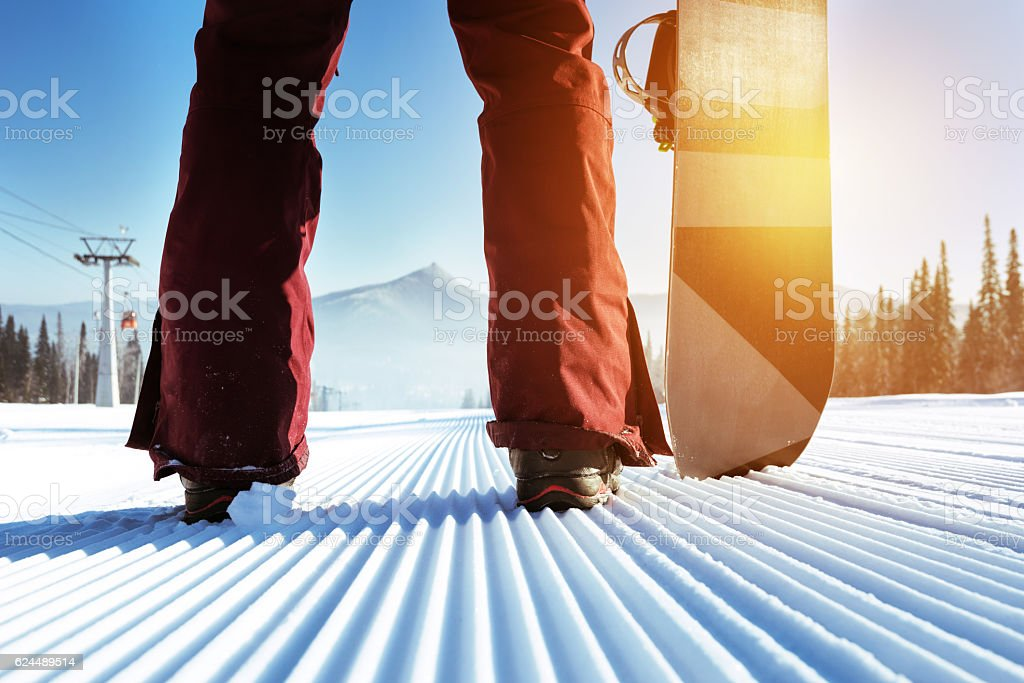 Snowboarder stands on slope backdrop stock photo