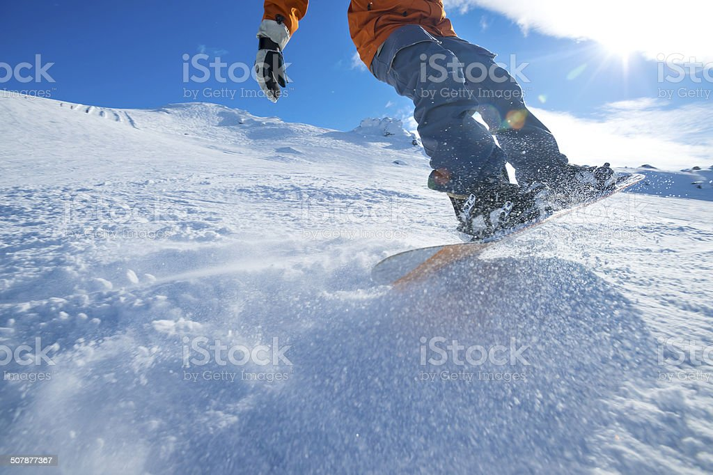 Snowboarder turning on a blue sky day stock photo
