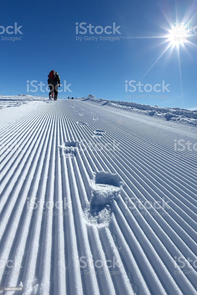 Snowboarder walks along prepared snow trace in mountains of Geor stock photo