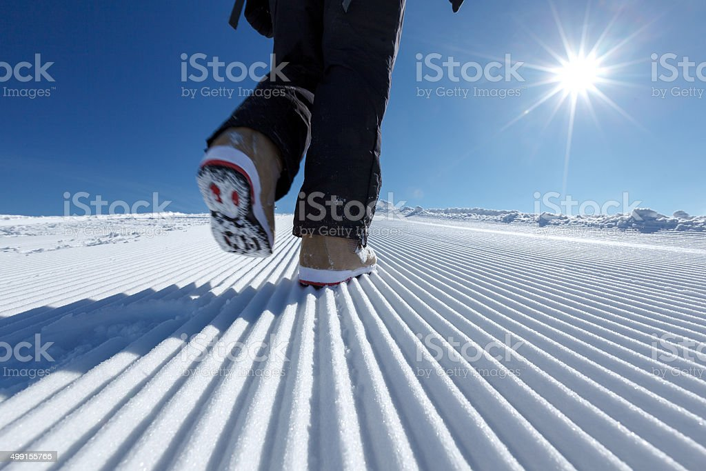 Snowboarder walks along prepared snow trace in mountains stock photo
