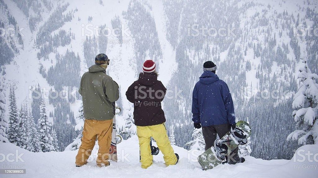 Snowboarders admiring mountainside stock photo