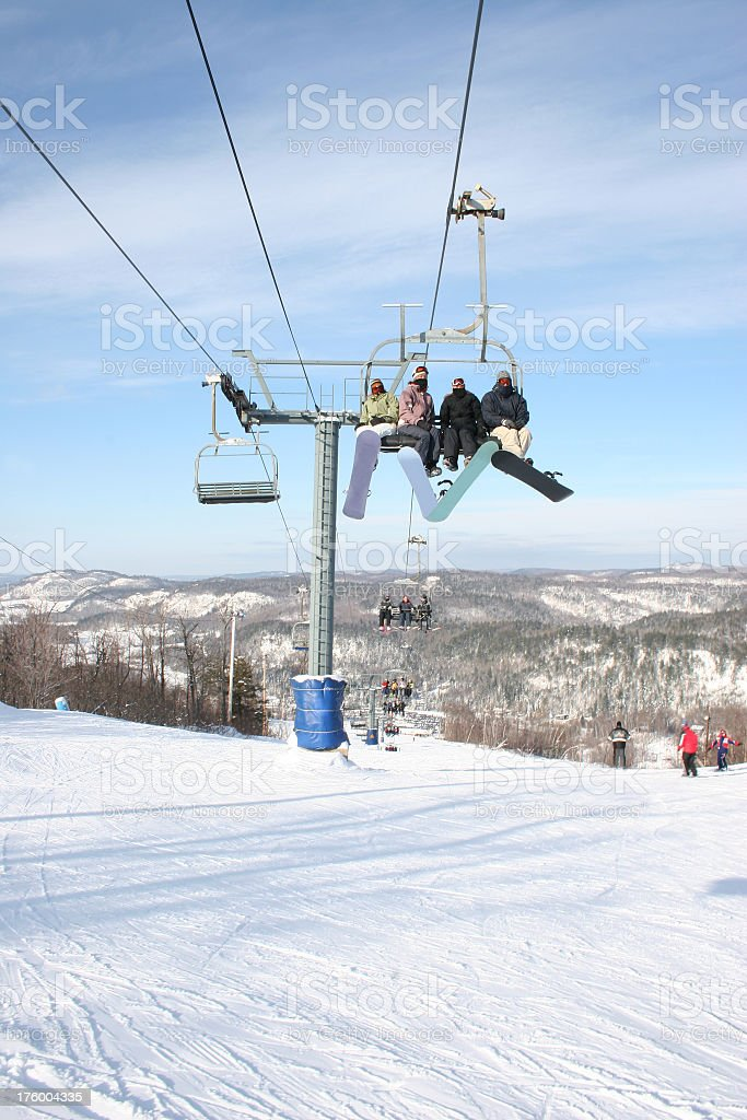 Snowboarders in a chairlift stock photo