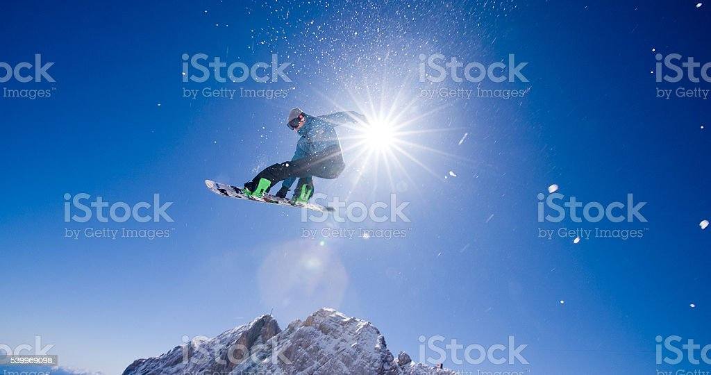 Snowboarder's jump stunt stock photo