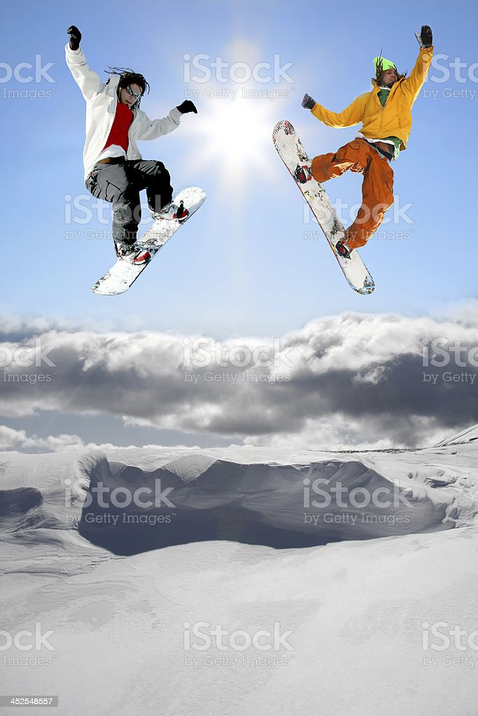 Snowboarders jumping against blue sky royalty-free stock photo