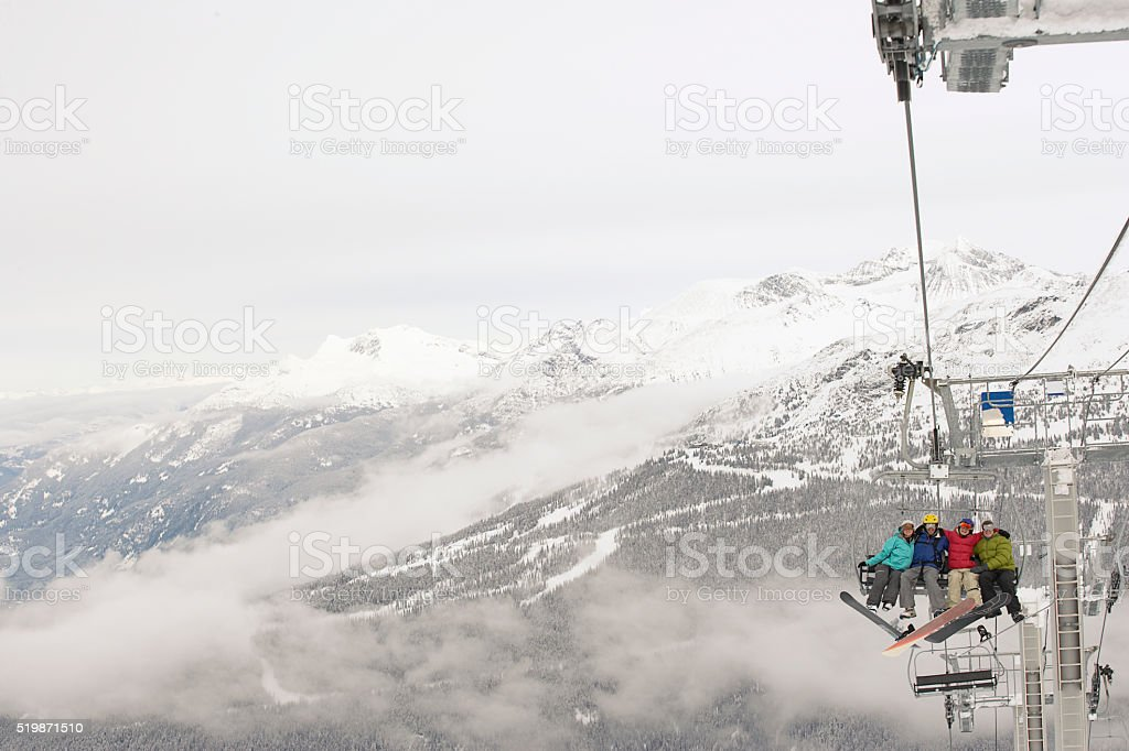 Snowboarders on a ski lift stock photo
