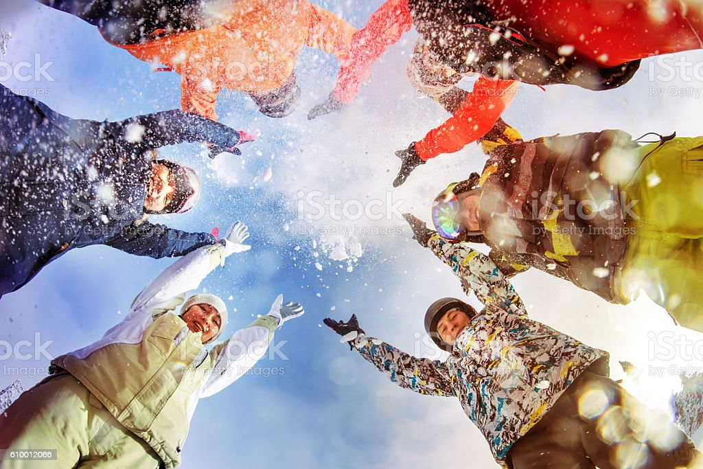 Snowboarders throw snow on blue sky backdrop stock photo