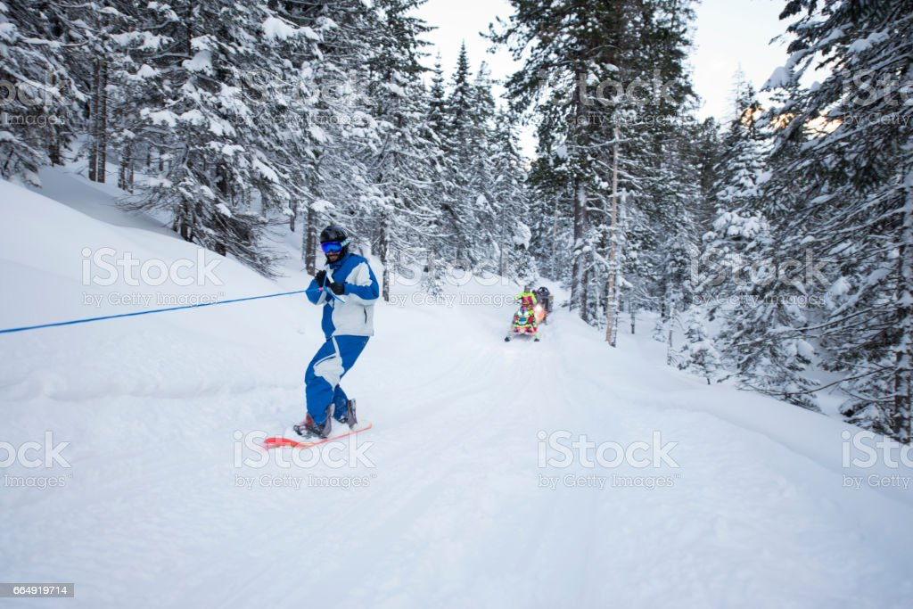 Man snowboarder riding a snowboard towed holding rope. Group of young...