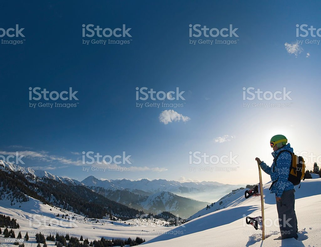 Snowboarding woman stands on top of snow covered mountain stock photo