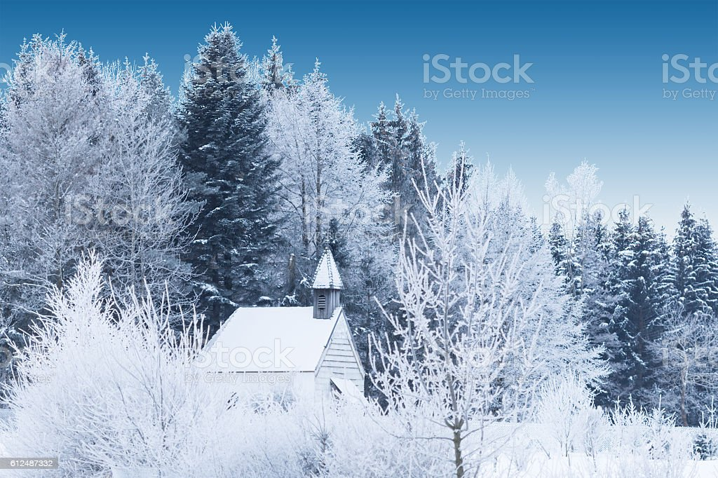 Snow-capped little wooden chapel in frosty winter forest stock photo