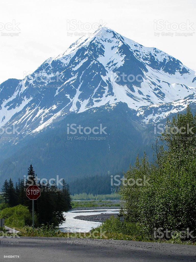 Snowcapped mountain with red stop sign at Exit Glacier, Seward stock photo