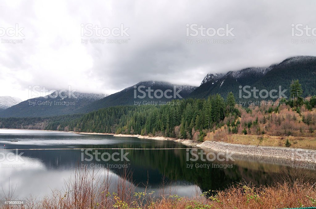 Snow-capped mountains by the reservoir stock photo