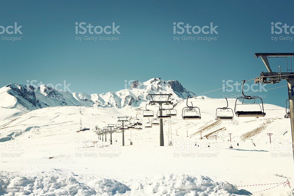 Snowcapped peak of a ski centre with lifts stock photo