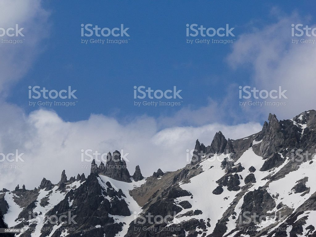 Snowcapped peak of Andes mountains with spiky rock formations. stock photo