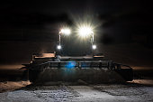Snowcat preparing a slope at night