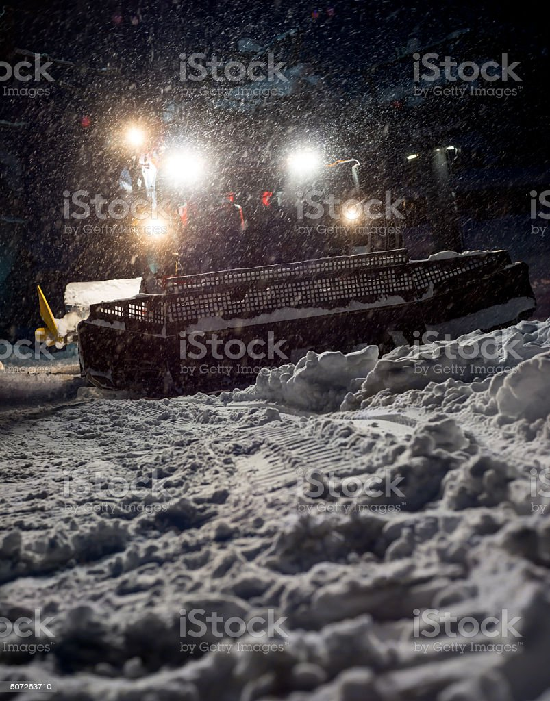 Snowcat preparing a slope in mountains stock photo
