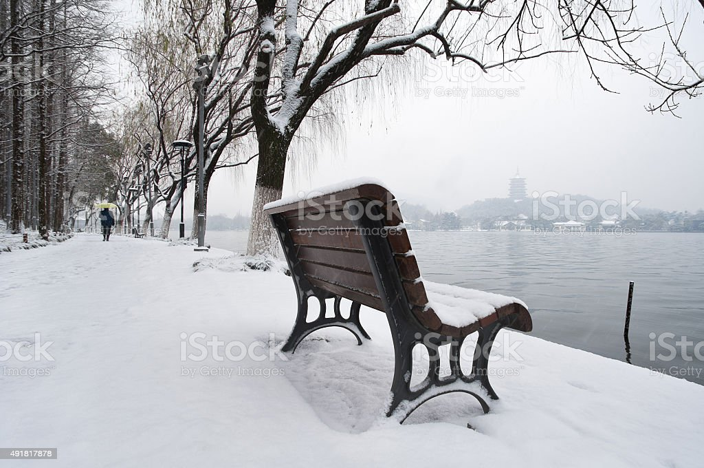 Snow-covered bench on the banks of West Lake, Hangzhou, China stock photo