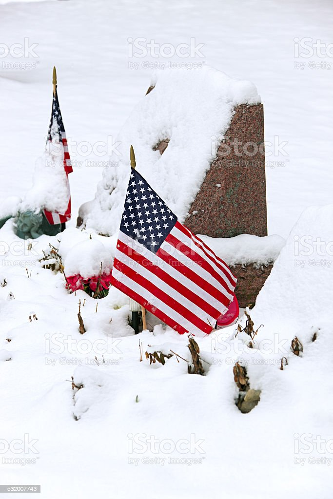 Snow-covered headstone (memorial) with US flags stock photo