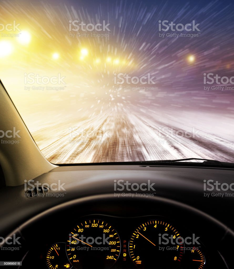 snow-covered road at night stock photo