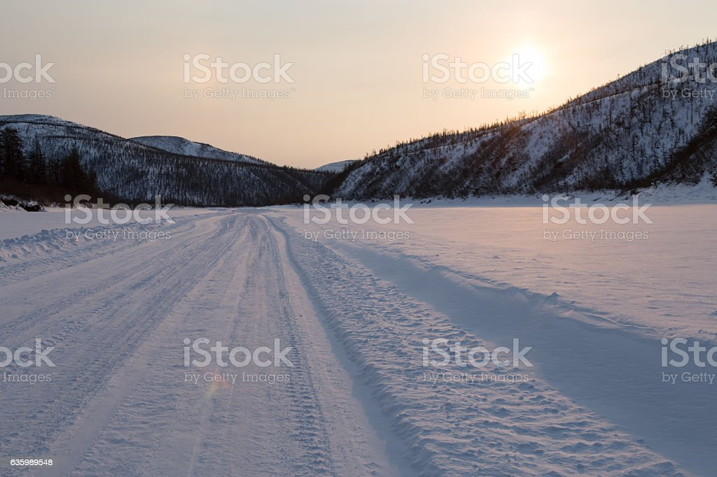 Snow-covered road on the river bed. stock photo