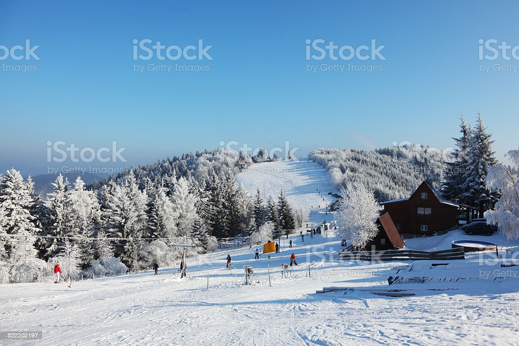 Snow-covered slope, lift cableway and a lot of skiers stock photo