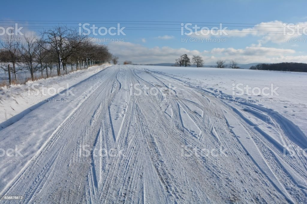 Snow-covered street in snowy scenery with  ripe tracks stock photo