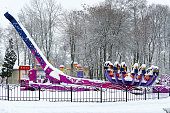 Snow-crowned attraction Zodiac in winter park during snowfall