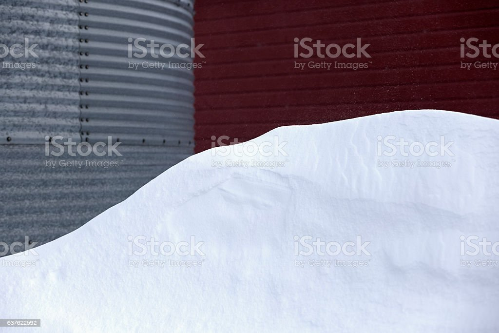 Snowdrift Next to Steel Grain Storage Bin and Red Barn stock photo