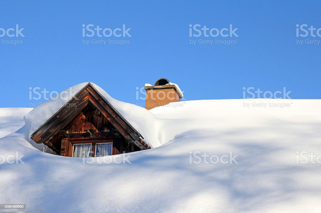 snowed roof window of an old wooden house stock photo