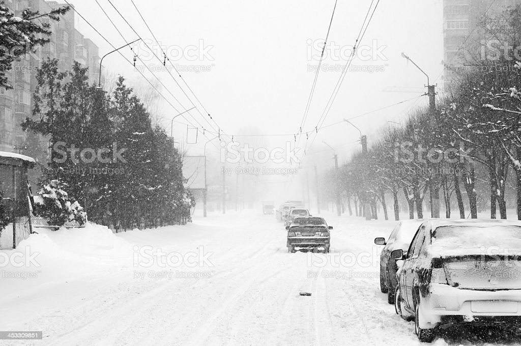 Snow-filled road with cars slowly moving along stock photo