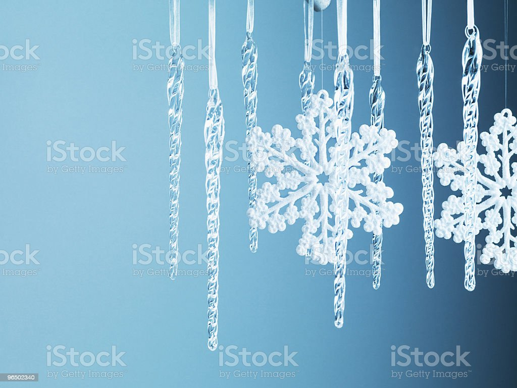 Snowflake and icicle Christmas ornaments hanging from string royalty-free stock photo