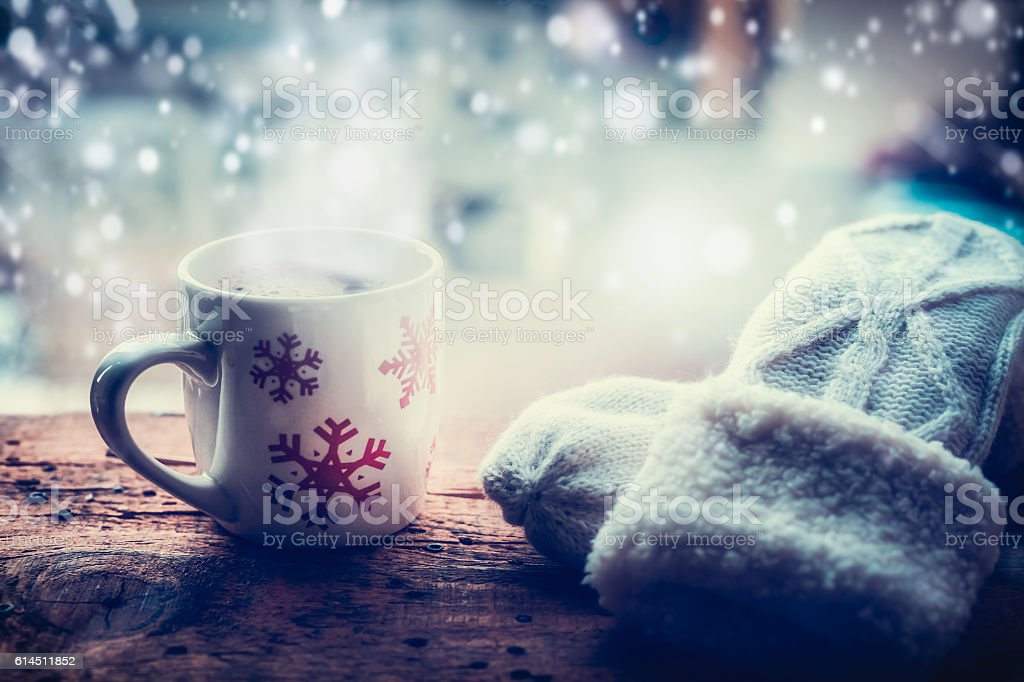 Snowflakes Mug with hot beverage and mittens on window sill stock photo