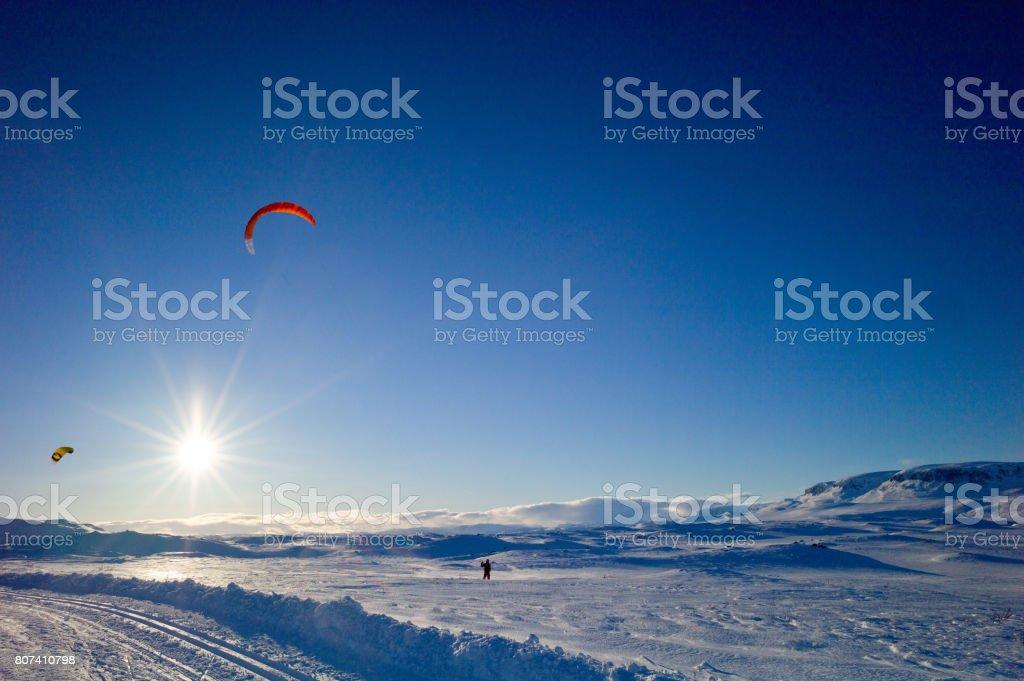 Snowkites in the sky at sundown stock photo