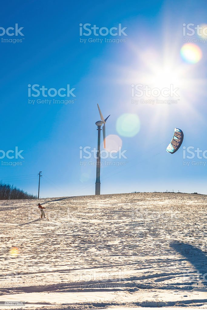 Snowkiting under a wind turbine and sun in winter day stock photo
