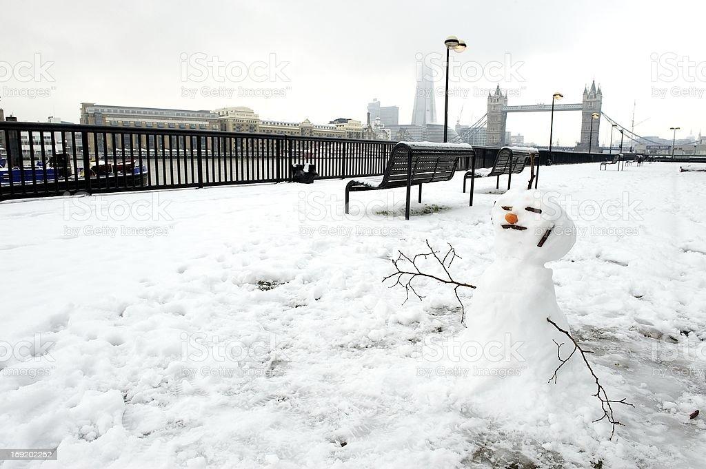 Snowman against Tower Bridge backdrop, London, UK royalty-free stock photo