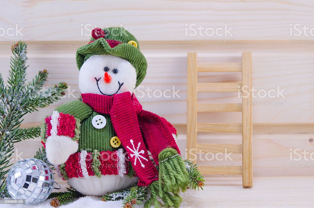 Snowman and a ladder ornamented with a fir branch royalty-free stock photo