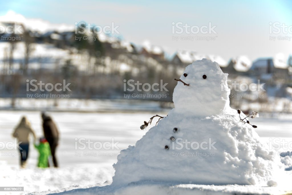 snowman and a young couple with a child stock photo