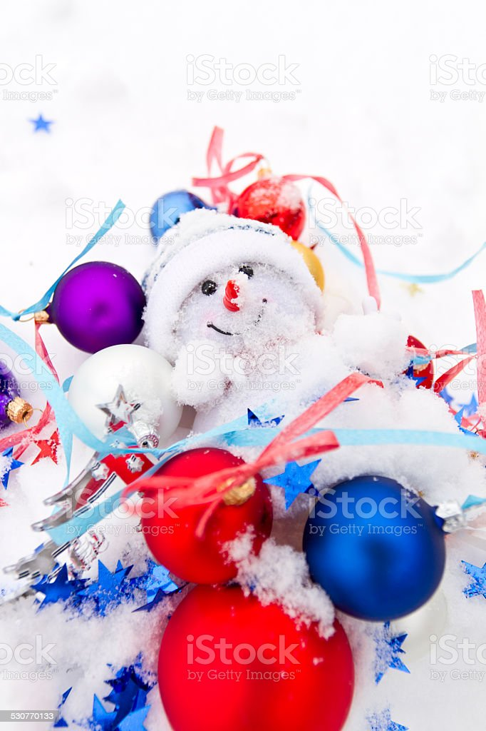 Snowman and multicolored Christmas balls in the snow stock photo