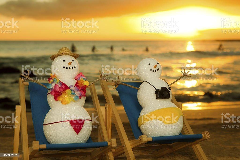 Snowman Couple on Winter Tropical Vacation, Enjoying Beach Paradise Sunset stock photo