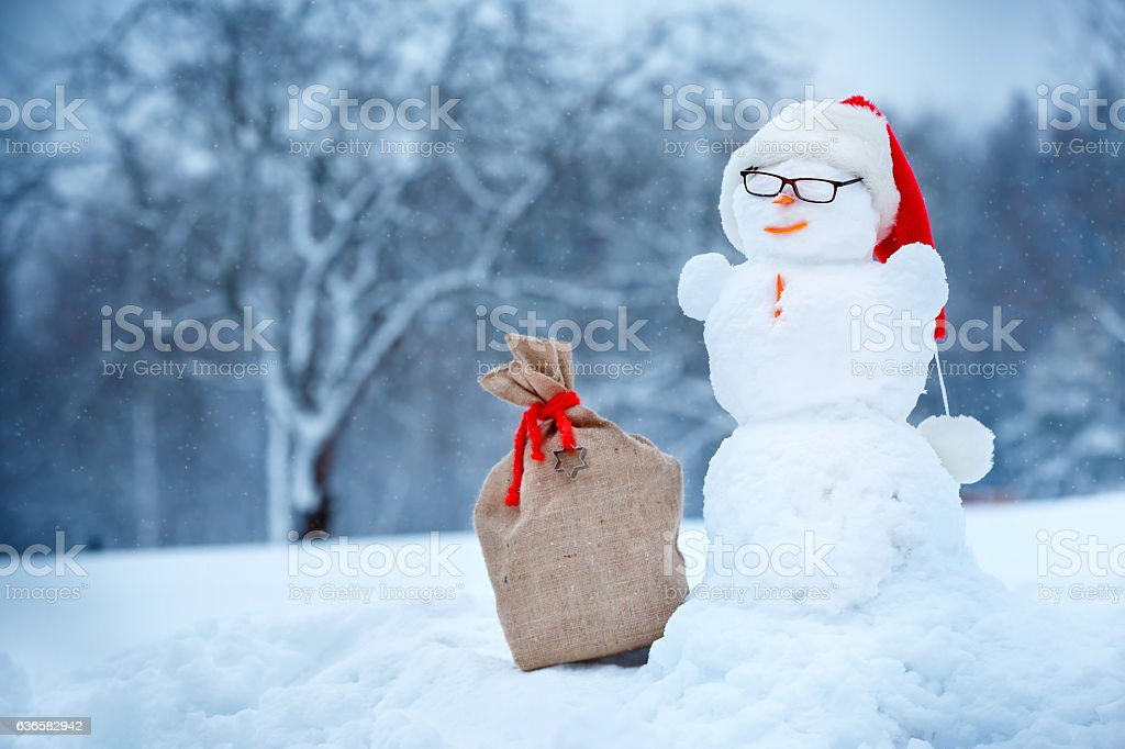 Snowman in Santa hat and sackcloth bag stock photo