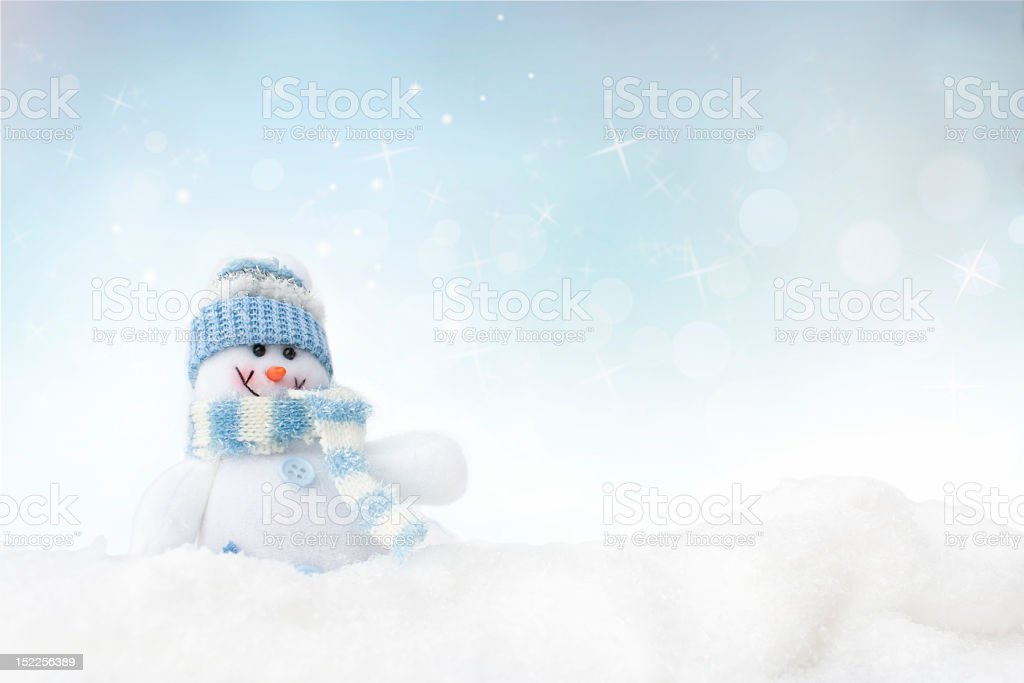 Snowman in white/blue scarf & hat against a winter setting royalty-free stock photo