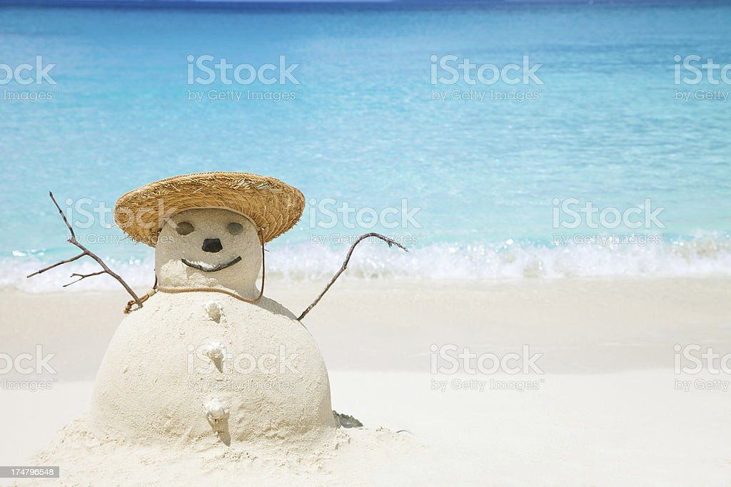 Snowman made of sand in straw hat at the beach stock photo
