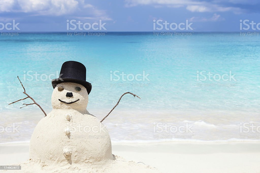 Snowman made of sand in top hat at a beach stock photo
