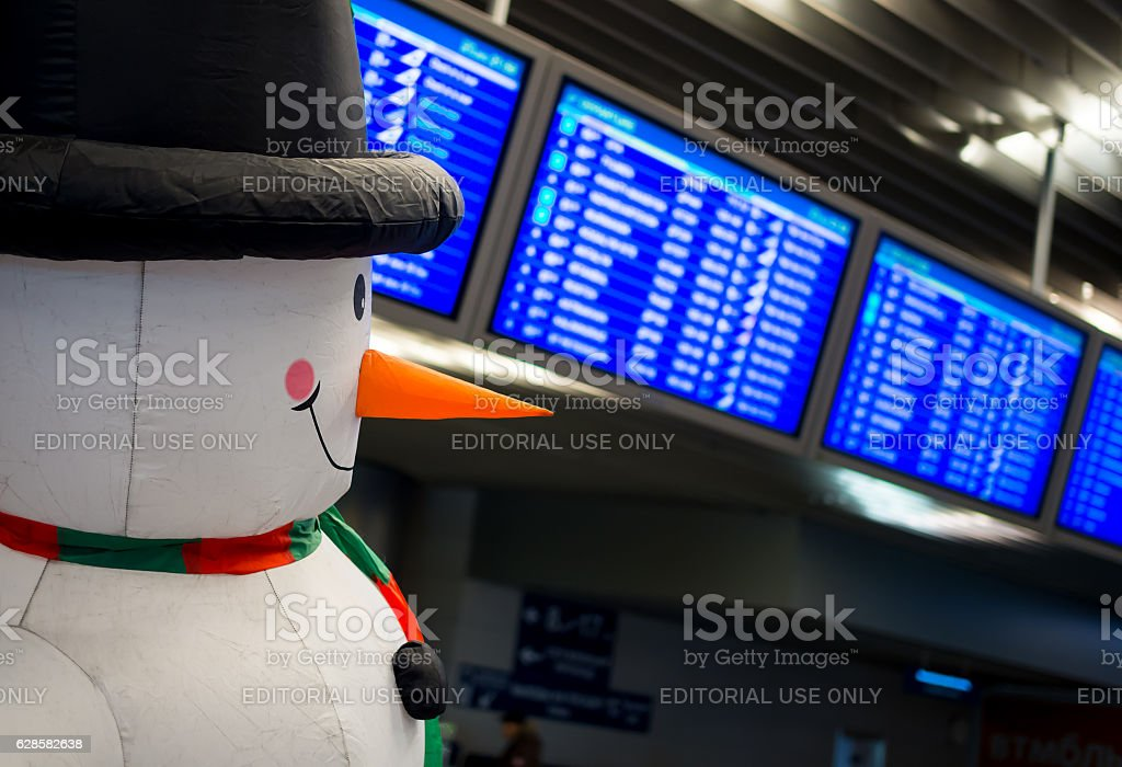 Snowman on the background of the schedule of flights stock photo