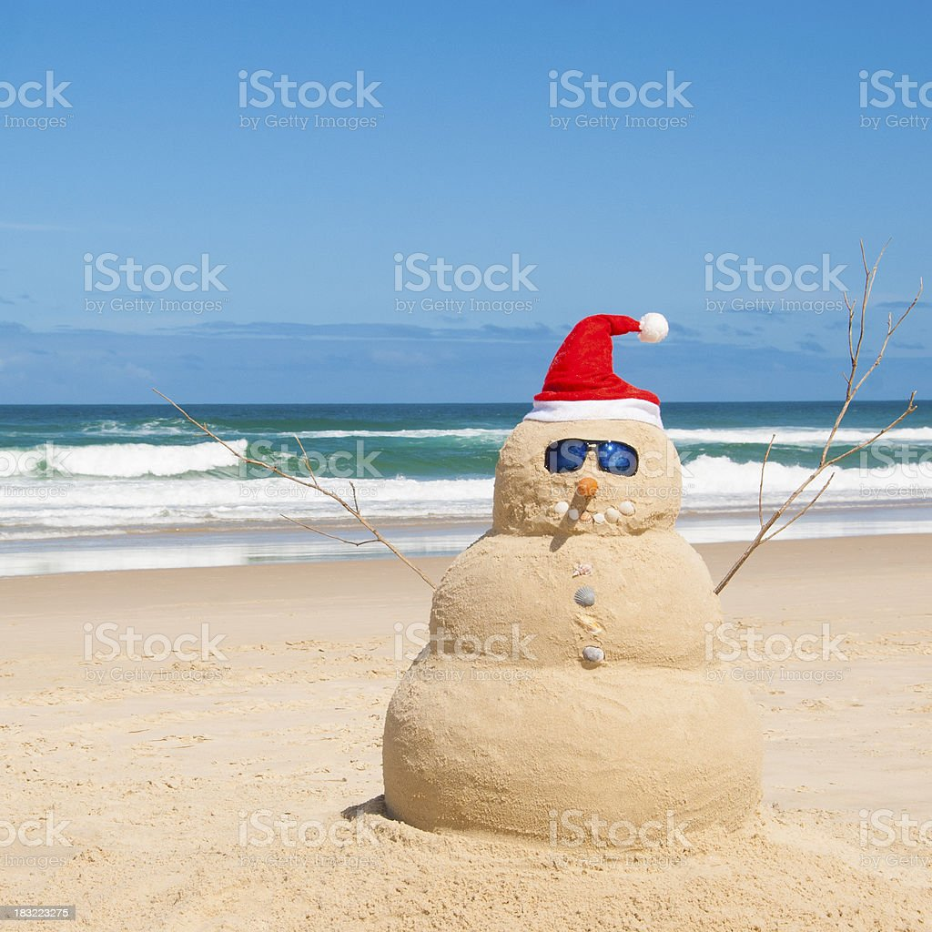 Snowman resists melting process on beach stock photo