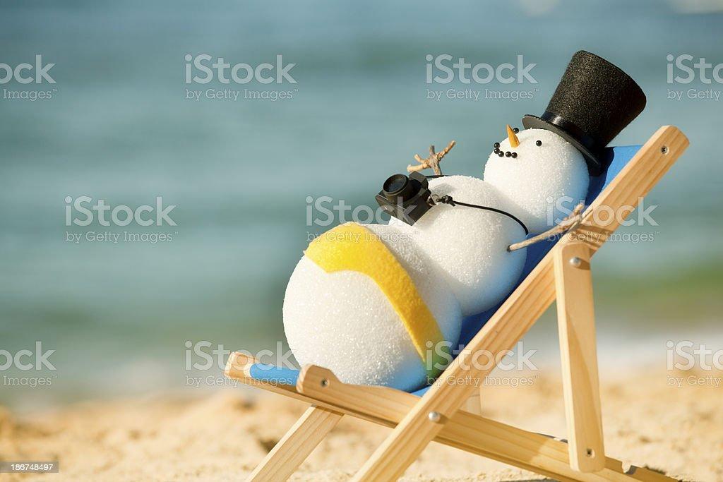 Snowman Sunning on Beach Chair, Enjoying Winter Seaside Tropical Vacation stock photo